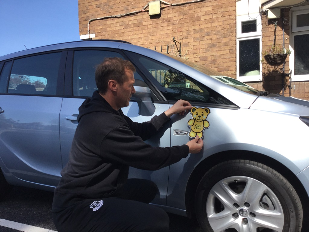 Duncan Ferguson applies Zoe's Place vinyls to their new car from Motorpoint