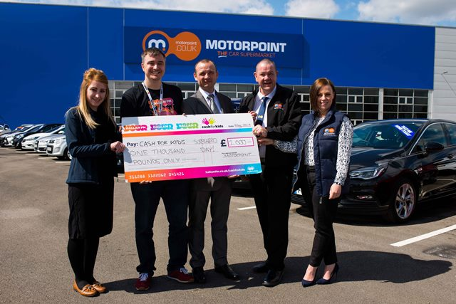 Jason Hurt, centre, presents a cheque for £1,000 to Allan Ogle from Cash for Kids at the new Motorpoint site in Sheffield
