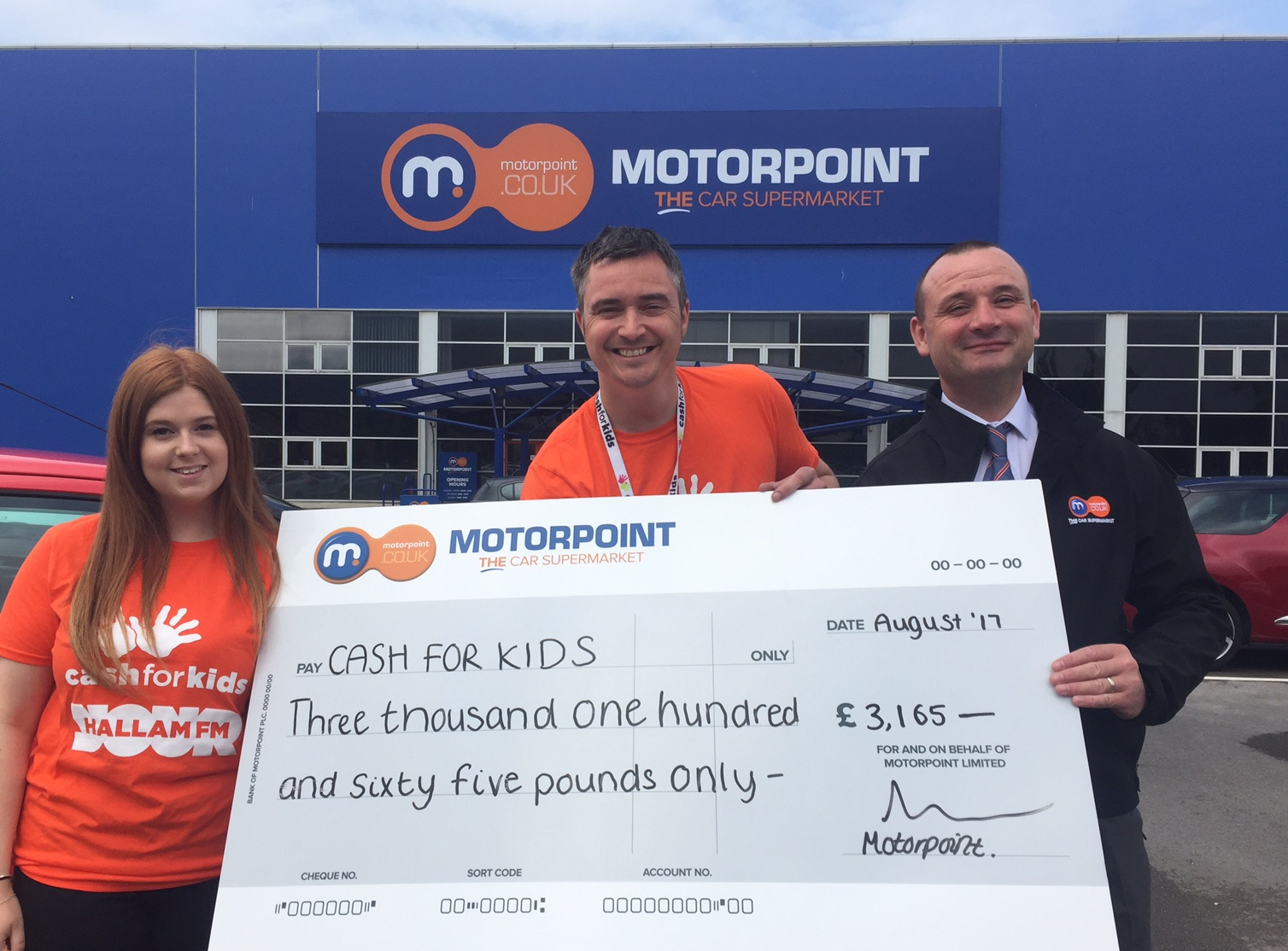 Allan Ogle, Charity Manager for Cash for Kids (centre) collects cheque from Motorpoint following the recent Drive In Cinema event at the company's newest branch