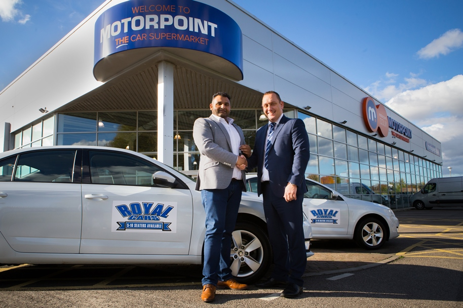 Imran Khan, left, from Royal Cars collects the keys to his 15 new car cars from Gavin Morgans, General Manager of Motorpoint in Birtley